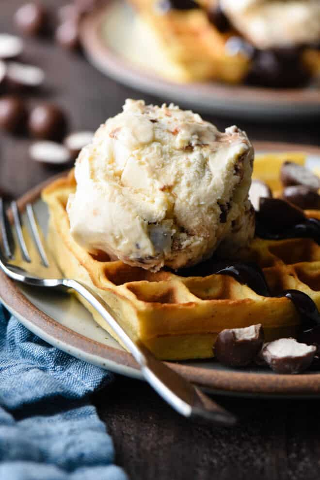 Cream colored plate with brown rim, with a waffle topped with chocolate sauce and a scoop of ice cream.