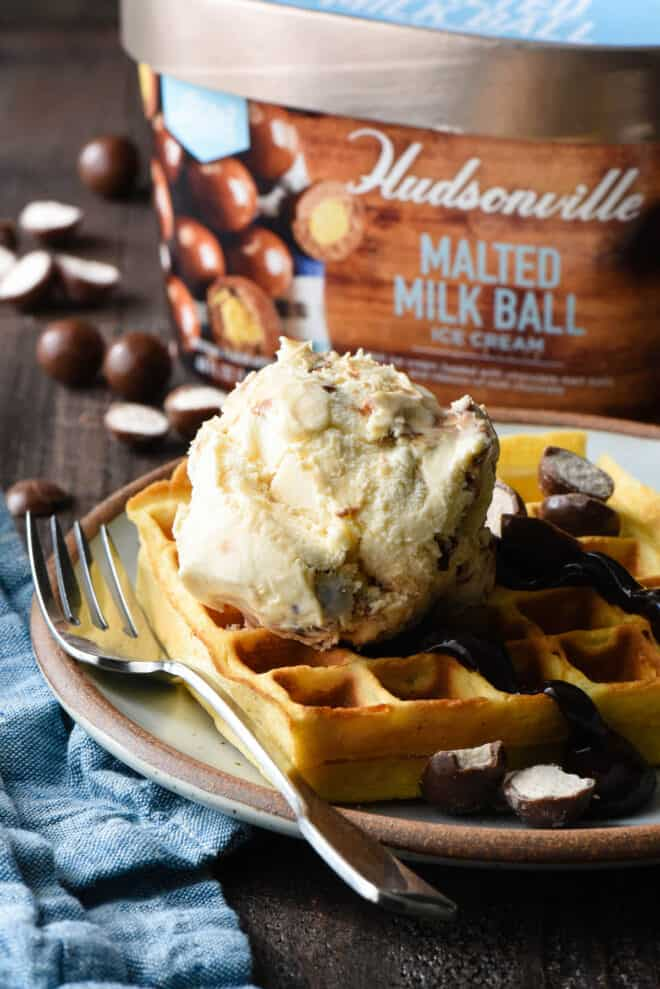 Waffle topped with hot fudge and ice cream on a plate, with a carton of Hudsonville Malted Milk Ball Ice Cream in the background.
