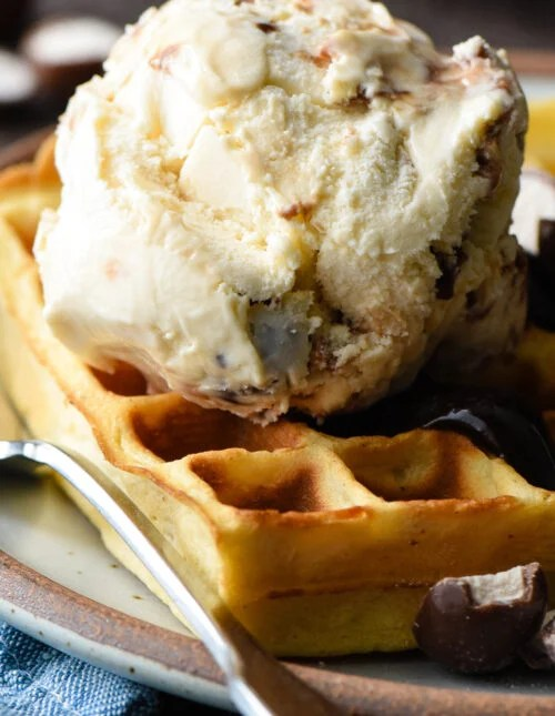 Golden brown waffle topped with hot fudge and a scoop of ice cream.