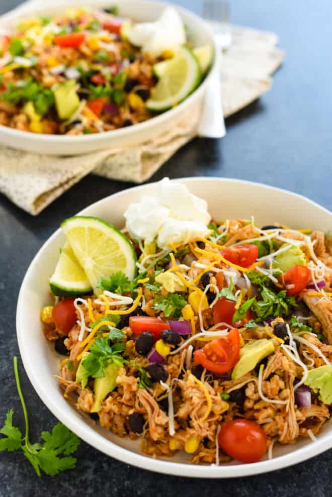 Two shallow bowls filled with a mixture of rice, beans, chicken and vegetables, garnished with sour cream and lime wedges.