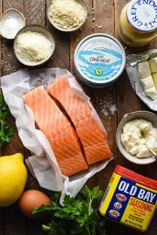 Ingredients for baked stuffed salmon, including salmon fillets, can of crab meat, parmesan cheese, bread crumbs, mustard, cream cheese, lemon egg and herbs.