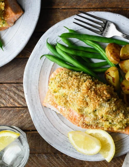 Rustic white plates topped with baked stuffed salmon, green beans and roasted potato wedges.