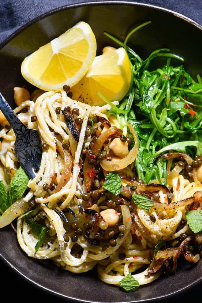 Spaghetti with Greek yogurt pasta sauce, topped with lentils, chickpeas, sliced lemons and herbs.