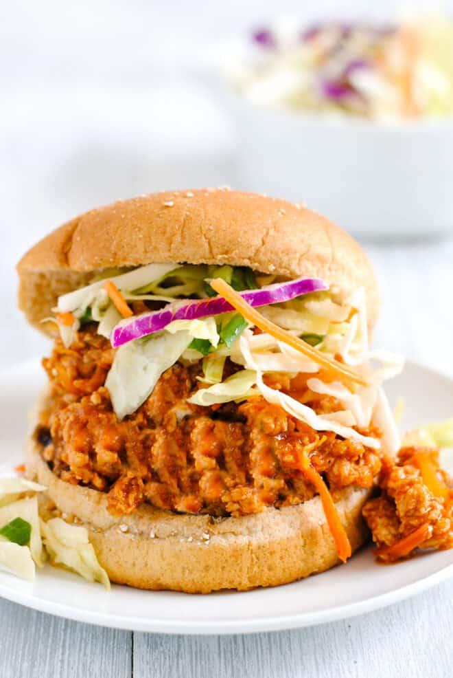 Wheat hamburger bun filled with Asian sloppy joe mixture and shredded vegetables.