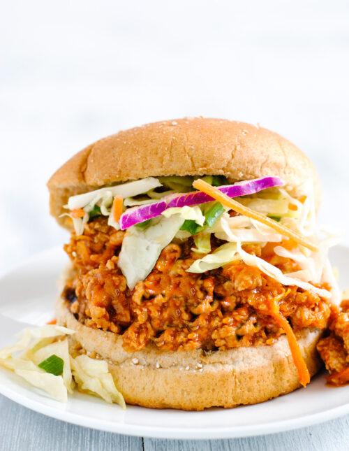 Wheat hamburger bun filled with orange hued chicken sloppy joe mixture and coleslaw.