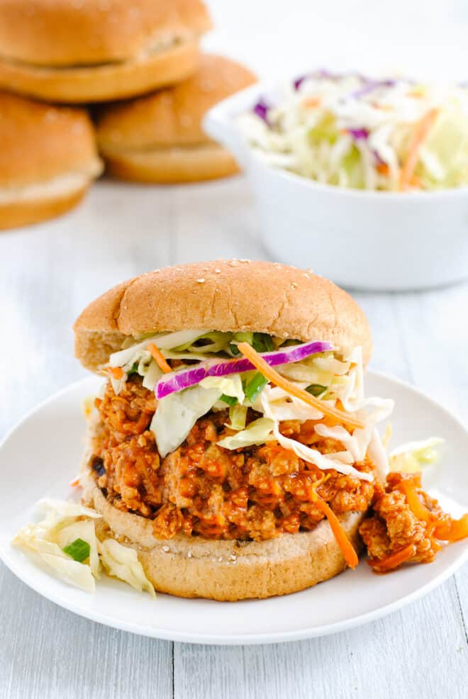 Chicken sloppy joe mixture in whole wheat bun, topped with coleslaw.