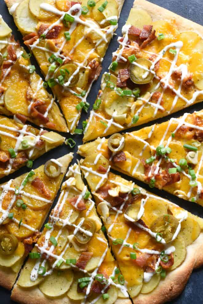 Closeup photo on savory pie topped with sliced spuds, bacon and ranch dressing.
