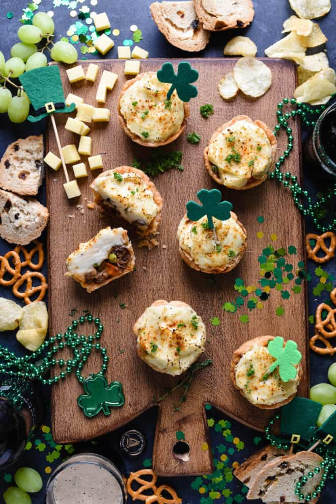 Festive St. Patrick's Day party scene with mini shepherd's pie, confetti, beads, pretzels, chips and beer.