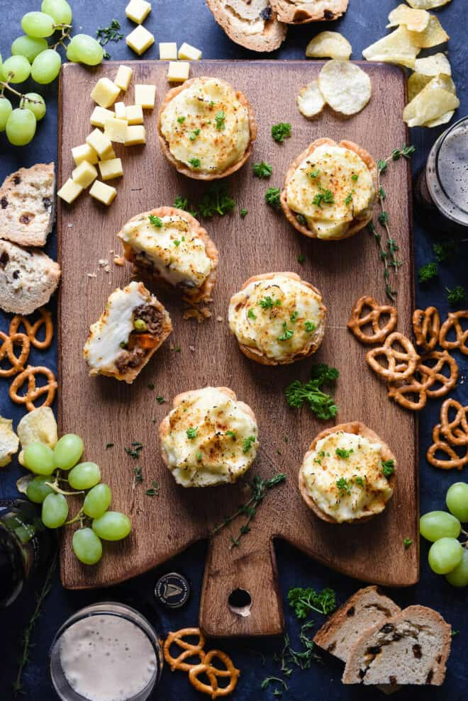 Small shepherd's pies on a wooden cutting board with party food like pretzels, chips, cheese and grapes.