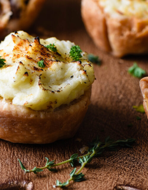 Mini shepherd's pie muffins on cutting board with thyme.