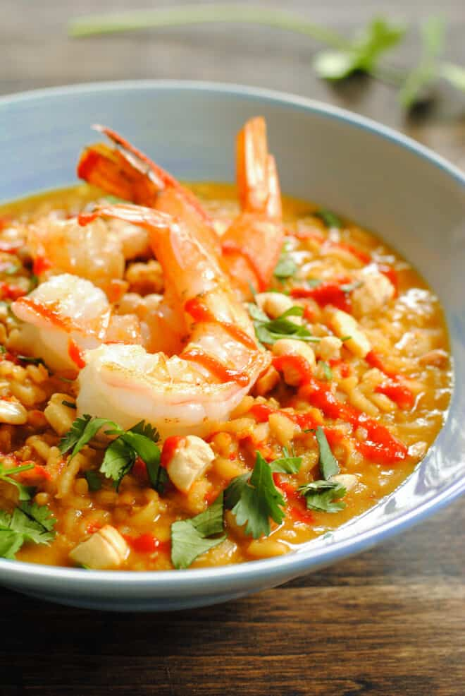 Shallow light blue bowl filled with richly orange colored risotto, topped with three large shrimp.