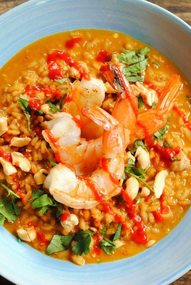 Three large shrimp on top of spicy orange rice dish, garnished with cilantro.