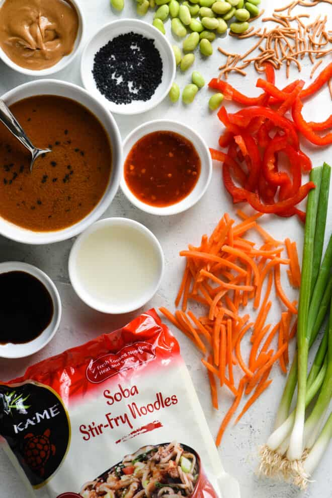 White tabletop filled with ingredients for cold noodle salad, including carrots, green onions, red pepper, edamame and Asian condiments.