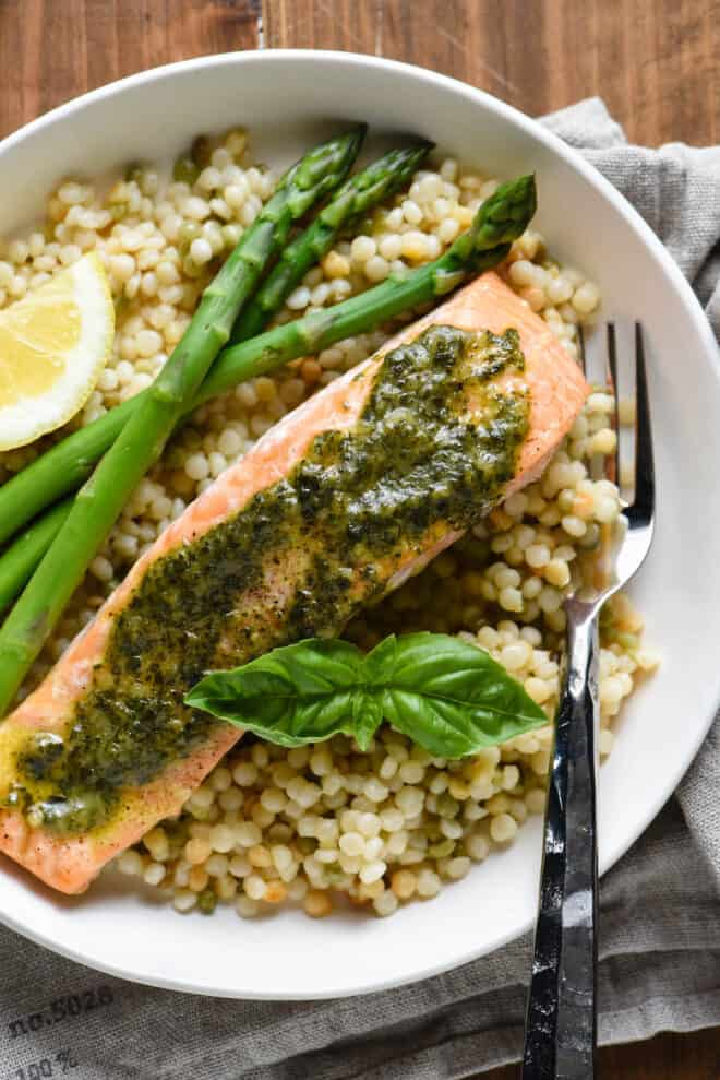 Shallow white bowl with pesto salmon, pearl couscous, asparagus spears and a lemon wedge.