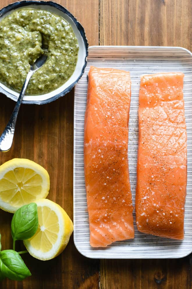 Small tray with two salmon fillets, bowl of basil pesto, halved lemon and fresh basil leaves, on wooden background.
