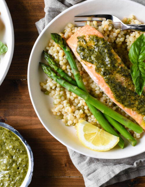 Shallow white bowls filled with pearl couscous, asparagus, and salmon topped with pesto sauce.