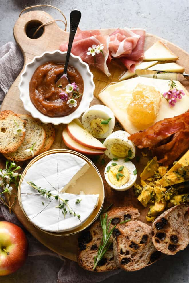 A breakfast charcuterie board arranged on a circular wooden board. Bread, cheese, hard boiled eggs, sliced apples, bacon and prosciutto cover the board.