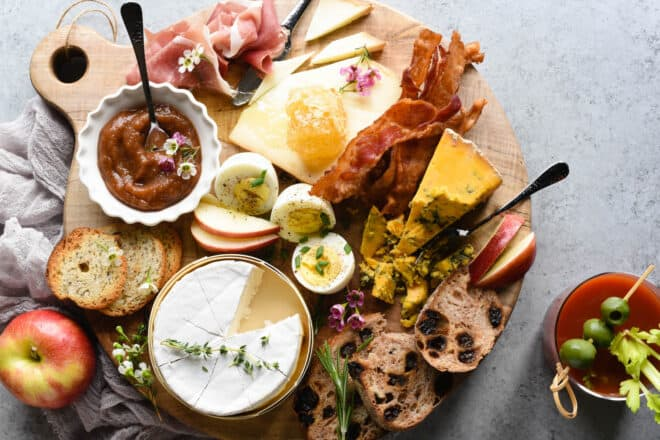A breakfast charcuterie board arranged on a circular wooden board. Bread, cheese, hard boiled eggs, sliced apples, bacon and prosciutto cover the board. A bloody mary is nearby.