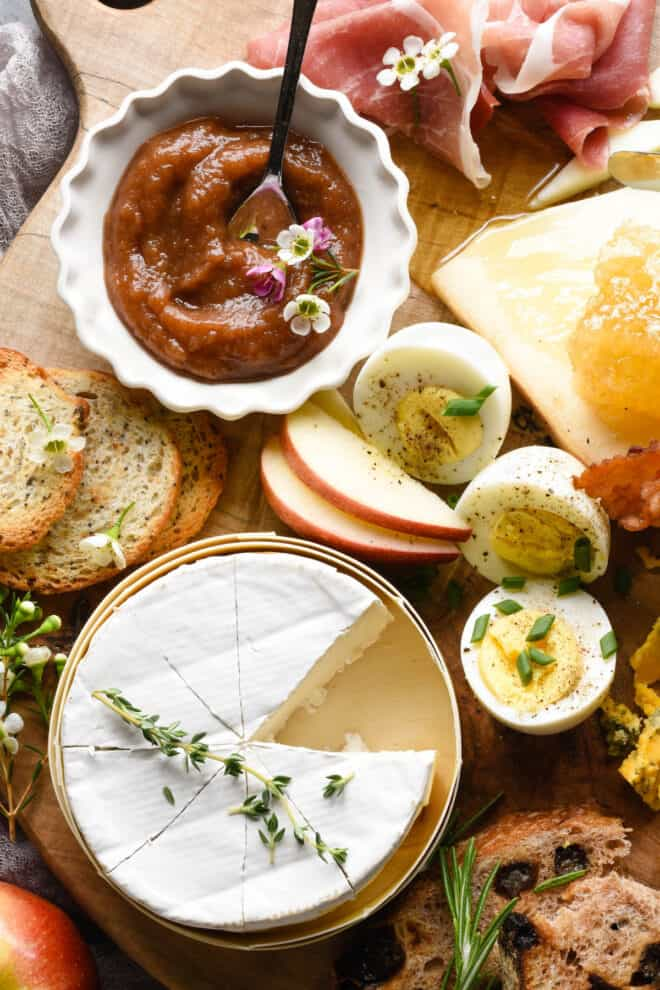 European breakfast items like cheese, eggs, apples and bread, on a wooden board.