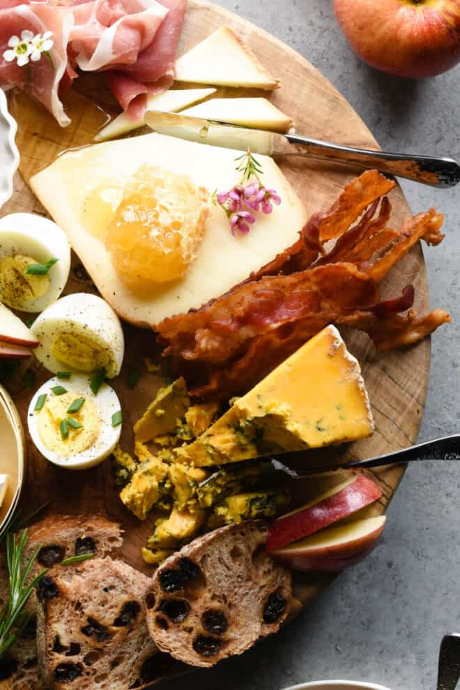 Wooden brunch board topped with cheese, bacon, honeycomb and hard boiled eggs.