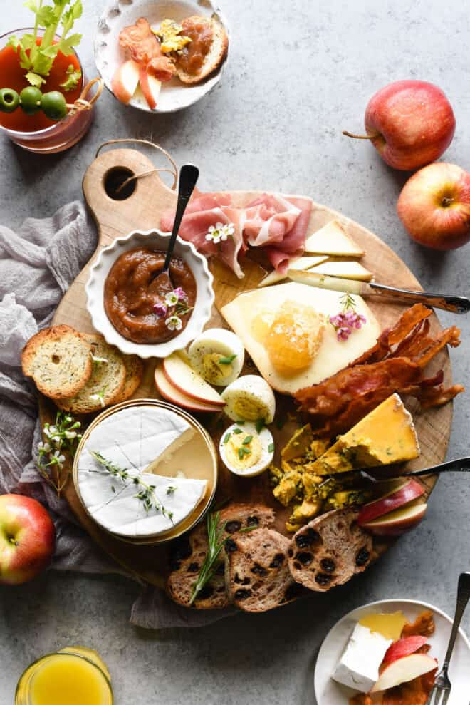 Round wooden cutting board filled with breakfast platter items like cheese, hard boiled eggs, bread, apple butter, bacon and prosciutto.