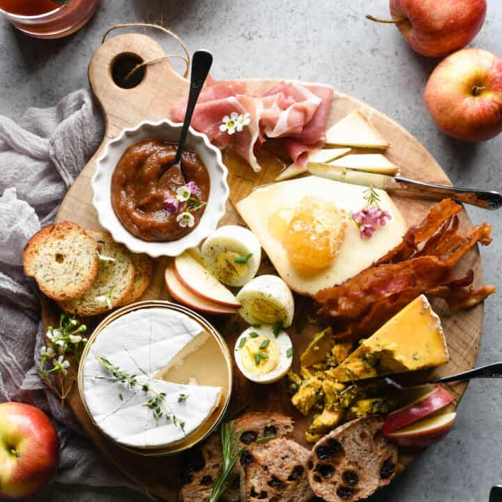 Round wooden cutting board filled with cheese, hard boiled eggs, bread, apple butter, bacon and prosciutto.