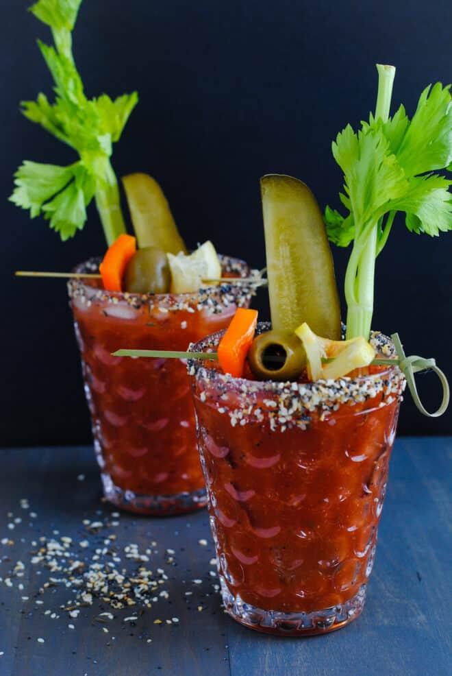 Two bloody mary cocktails with everything bagel rim salt and garnishes like celery, pickles and olives.