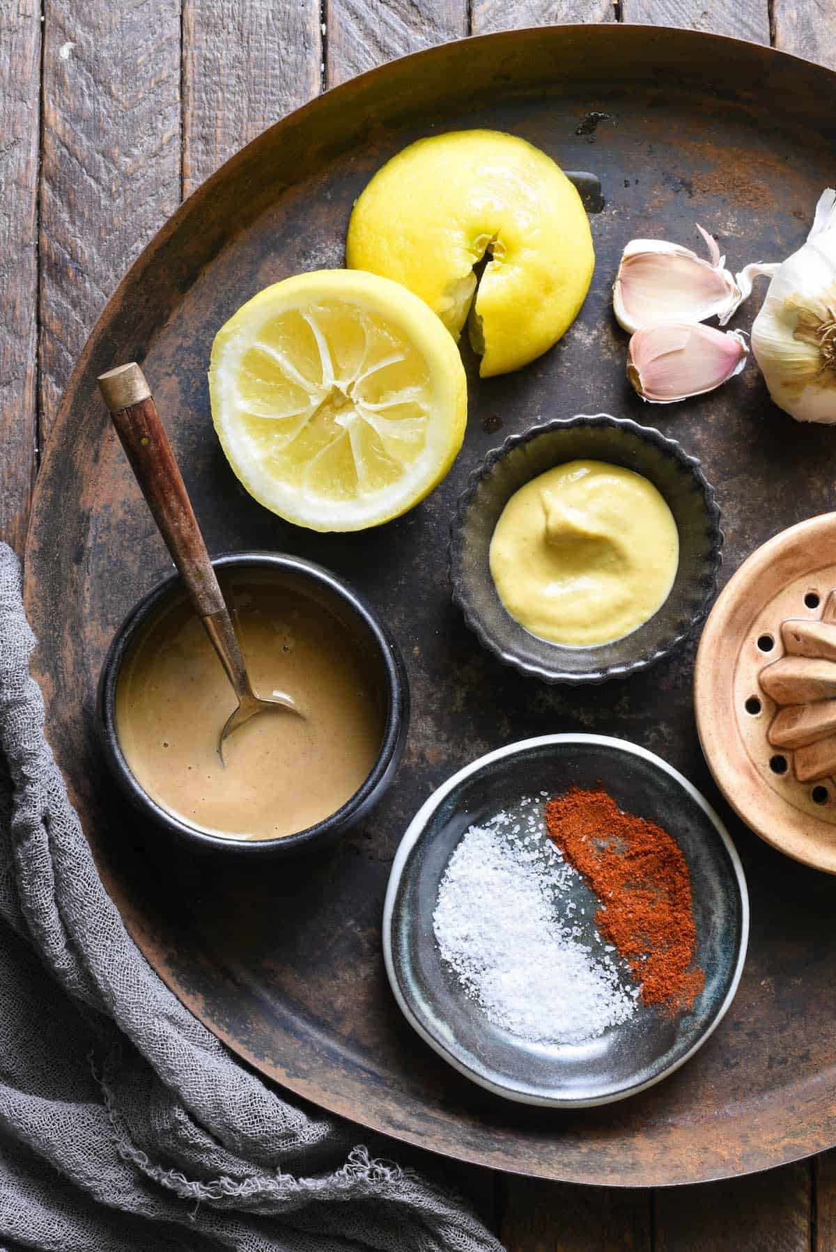 Overhead shot of ingredients for lemon tahini dressing. Tahini, salt and paprika, dijon mustard, lemon halves and garlic cloves.