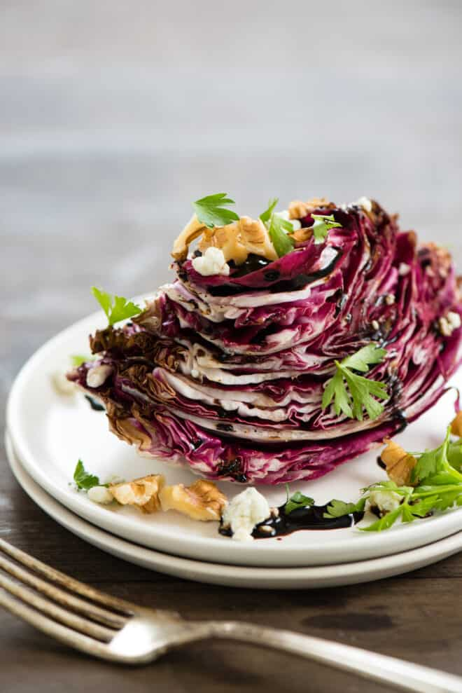 Wedge of radicchio topped with balsamic glaze, nuts, cheese and herbs.