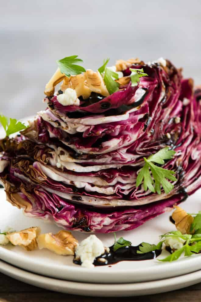 Wedge of Italian chicory topped with balsamic glaze, nuts, cheese and herbs.