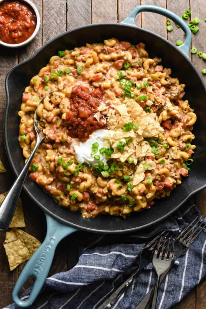 Large skillet filled with taco mac and cheese, toped with salsa, sour cream crushed tortilla chips and green onions.