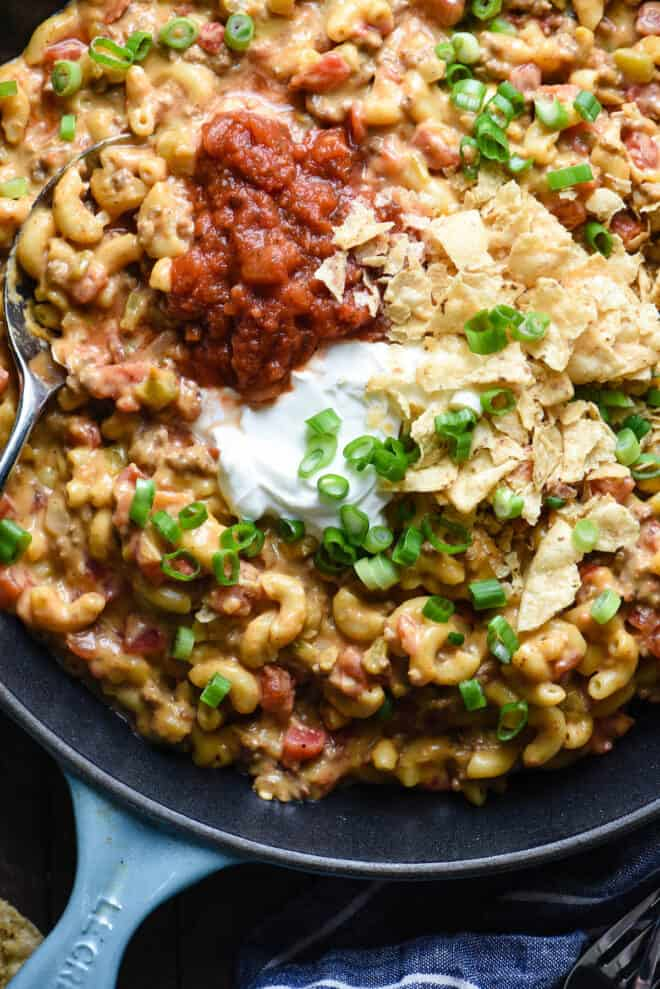 Closeup on elbow macaroni and cheese with ground beef, topped with salsa and sour cream.