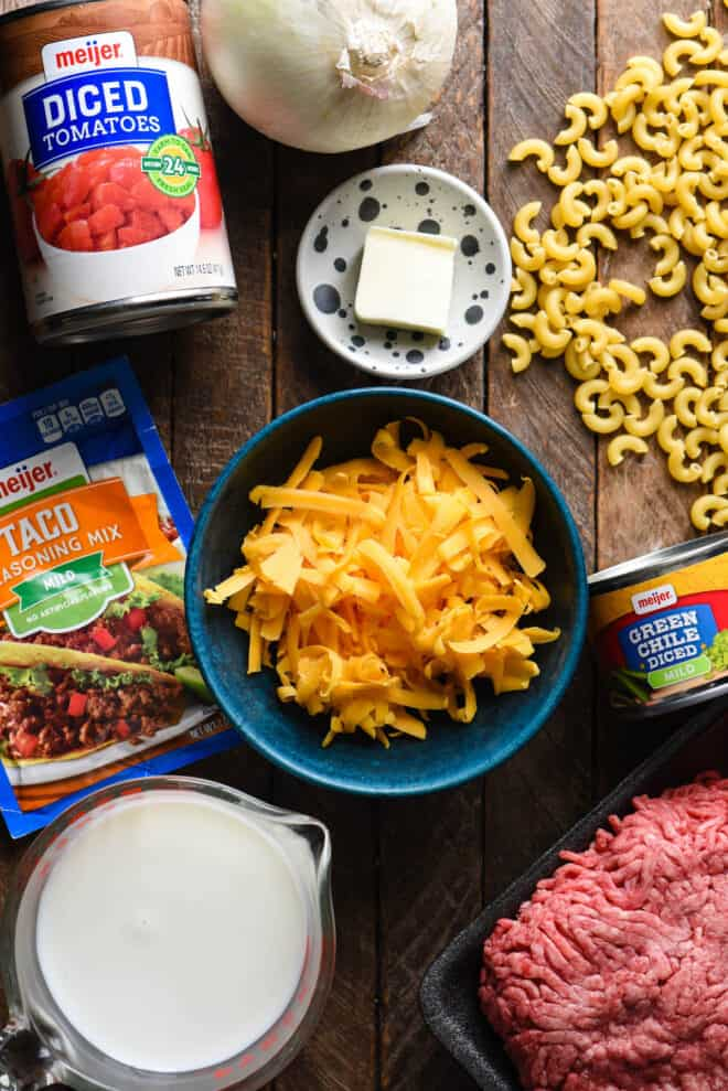 Wooden background with ingredients arranged on it, like shredded cheese, elbow noodles, taco seasoning mix, canned tomatoes and green chiles, butter, ground beef and onion.