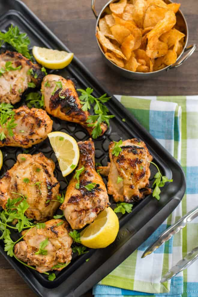 Large black tray of grilled chicken that has been soaked in buttermilk chicken marinade, with potato chips and tongs nearby.