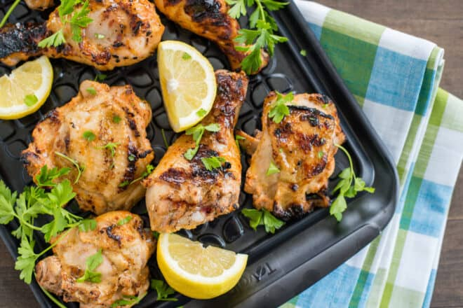 Black tray of buttermilk grilled chicken garnished with parsley and lemon wedges.