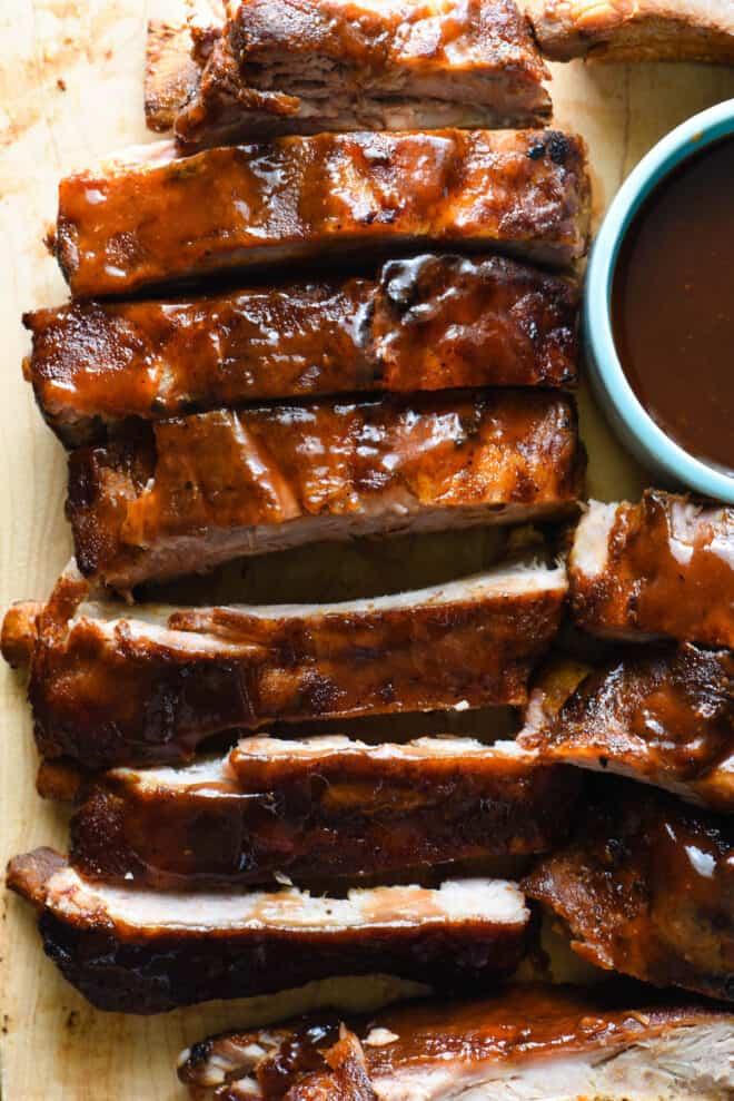 Close up on wooden cutting board with cut crock pot ribs glazed with sauce.