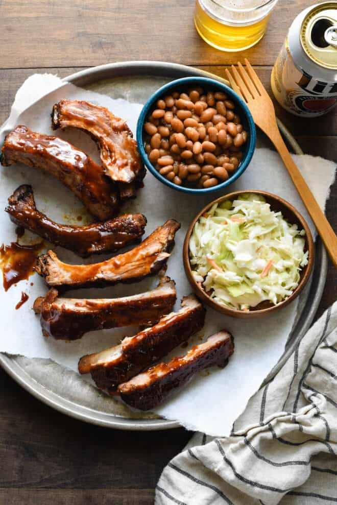 Large metal tray filled with slow cooker ribs, coleslaw and baked beans.