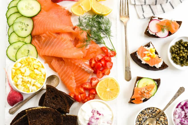 A party spread featuring a smoked salmon platter and pumpernickel bread.