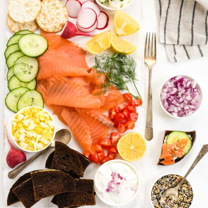 White table and cutting board topped with smoked salmon and garnishes like cucumber, capers, vegetables, cream cheese, bread and crackers.