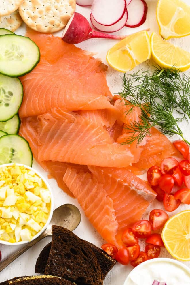 Closeup on sliced smoked salmon, chopped eggs, dill, tomatoes, cucumbers and lemon wedges.