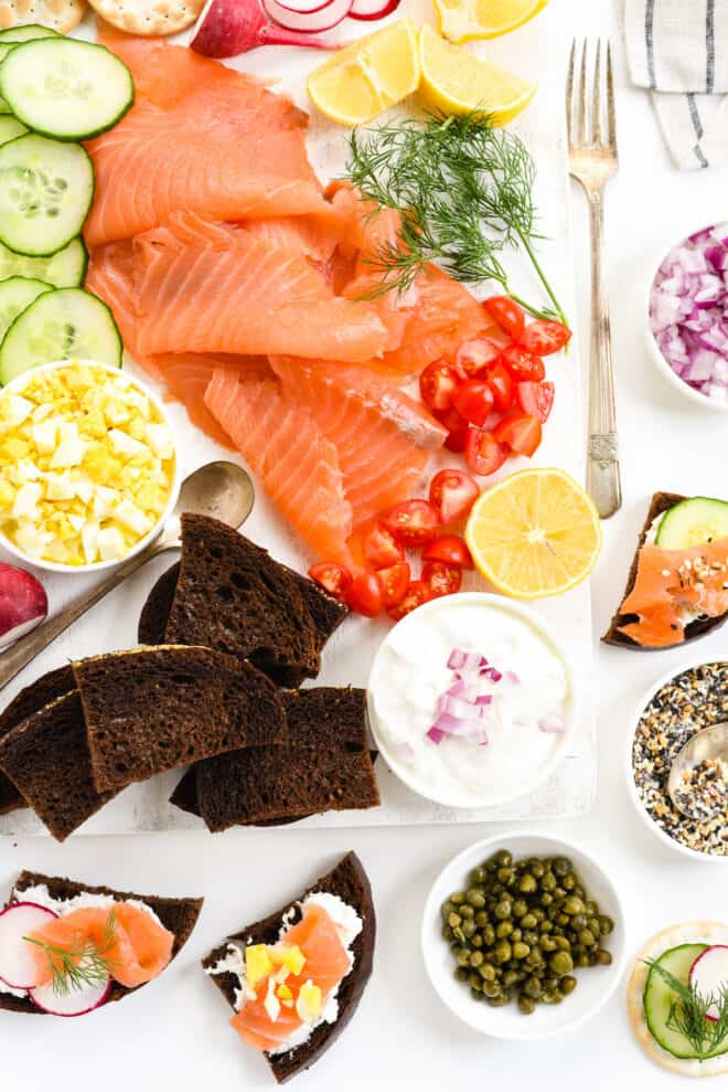 An appetizer platter with sliced lox, hard boiled egg, sliced cucumbers, chopped tomato, dill and brown bread.