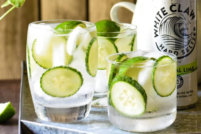 Closeup on three White Claw cocktails garnished with limes and cucumbers.
