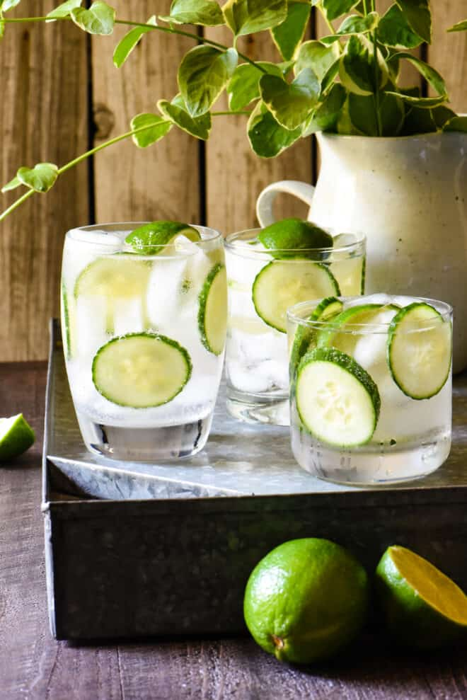 Three cocktails on a tray, garnished with lime wedges and cucumber slices.