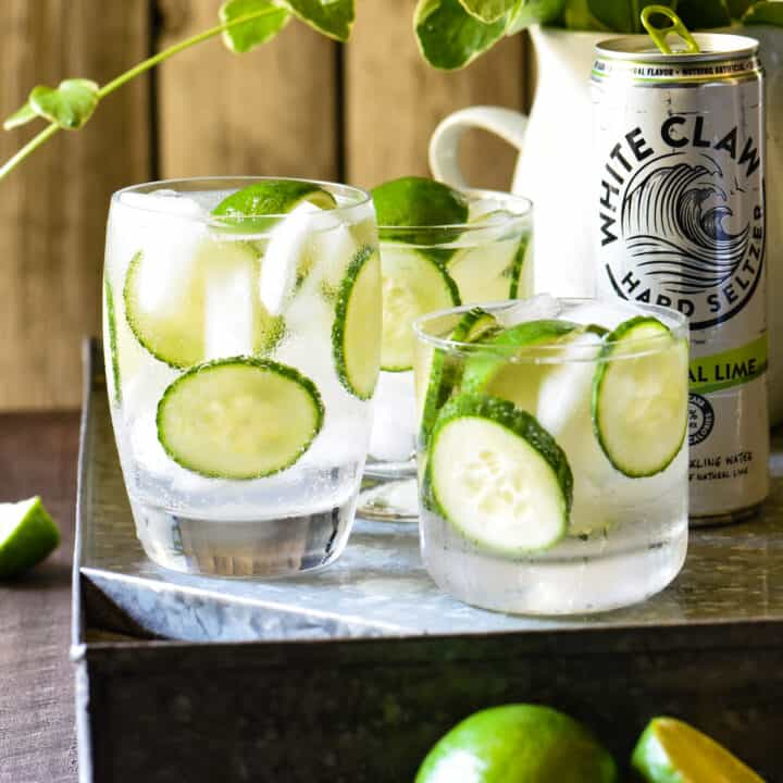 Three glasses filled with limes, cucumbers and clear liquid, with a can of White Claw next to them.
