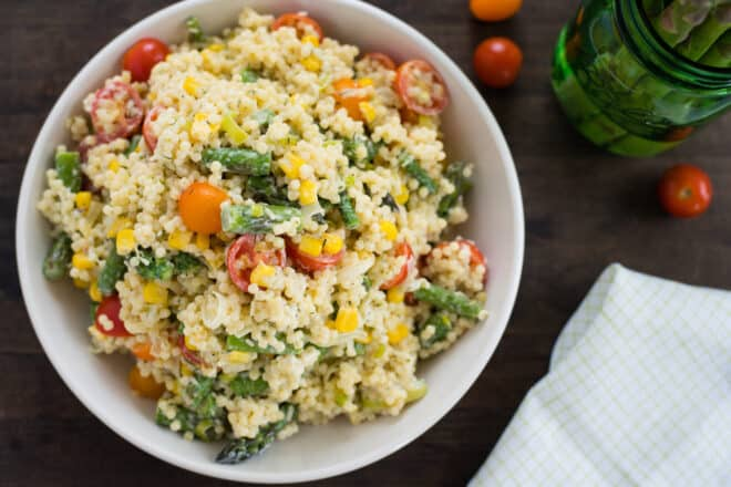White bowl filled with acini di pepe pasta salad with tomatoes, asparagus and corn.