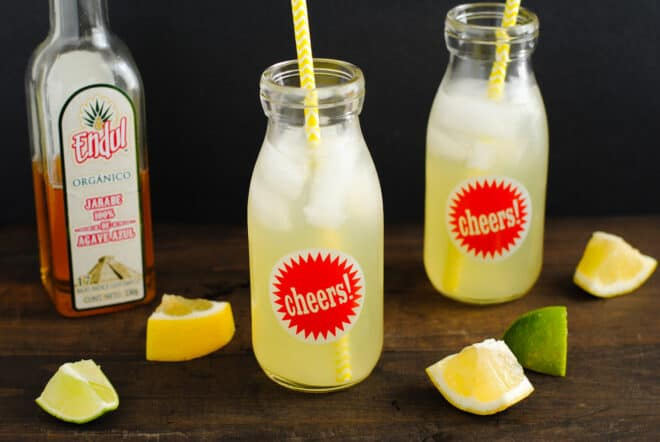 Bottle of agave nectar, and two glass bottles filled with lemonade and yellow straws.