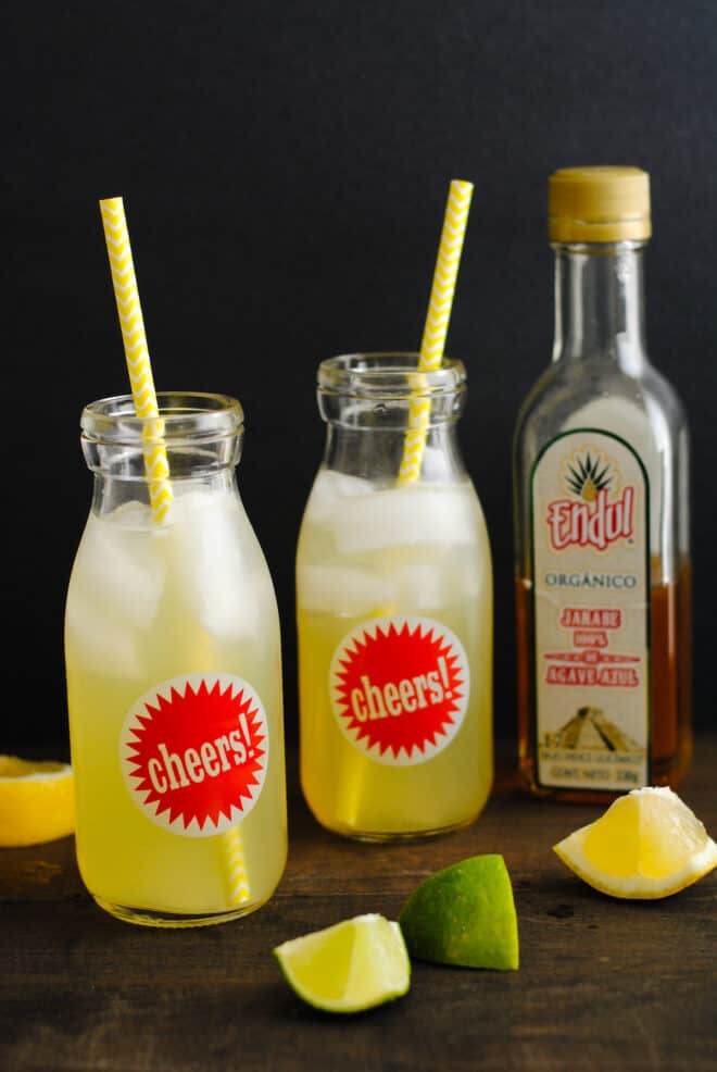 """Two small glass bottles with """"cheers"""" labels on them, filled with a yellow liquid, ice, and decorative paper straws. A bottle of agave nectar is in background."""