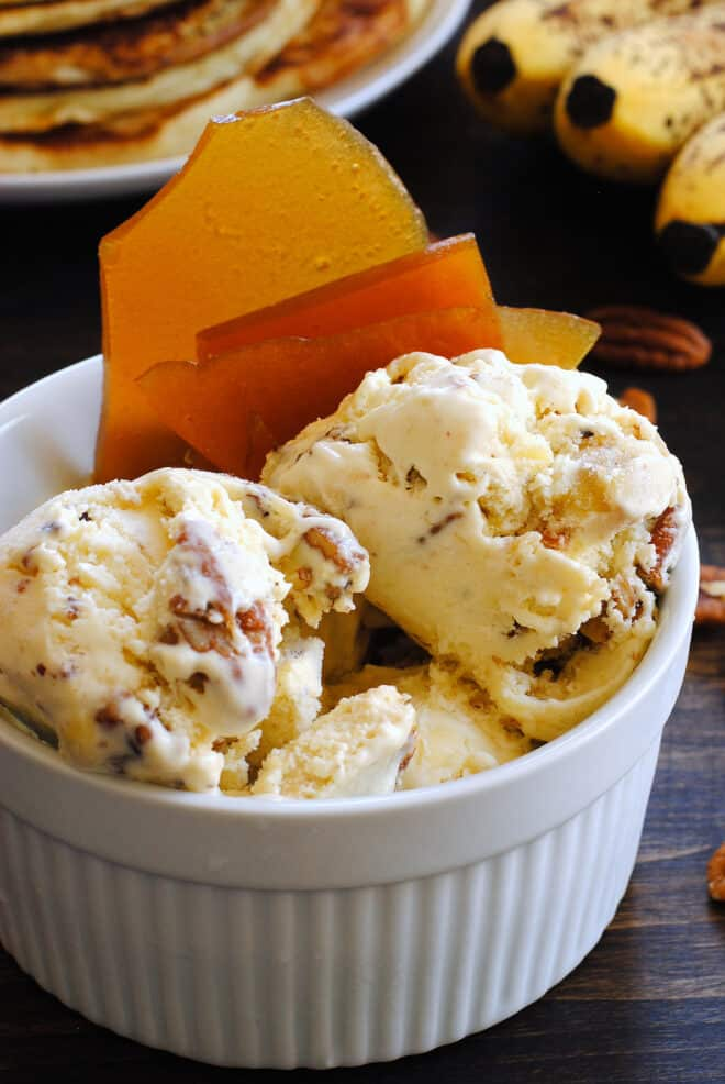 White ceramic bowl filled with nutty homemade gelato and garnished with brown brittle.