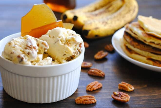 Large white ramekin filled with pancake ice cream, garnished with brittle. Bananas, pancakes and pecans garnish the scene.