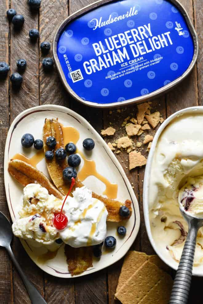 Small oblong shaped white plate topped with browned bananas, ice cream, blueberries, caramel sauce and a cherry. A container of Blueberry Graham Delight ice cream is next to plate.